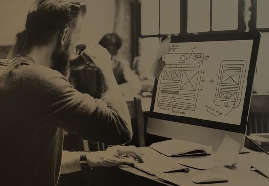 Man looking at wireframes on his computer